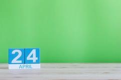 24 de abril Dia 24 do mês, calendário na tabela de madeira e fundo verde Tempo de mola, espaço vazio para o texto Imagens de Stock