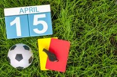 15 de abril Dia 15 do mês, calendário no fundo da grama verde do futebol com equipamento do futebol Tempo de mola, espaço vazio Imagem de Stock