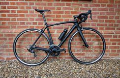 28 de abril de 2019 - Londres, Reino Unido: Situación negra elegante de la bicicleta contra la pared de ladrillo resistida foto de archivo libre de regalías