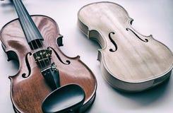 De abstracte achtergrond van het kunstontwerp van ruwe viool zette naast voltooide viool stock foto
