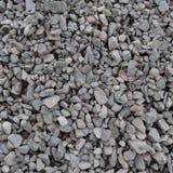 De abstracte grijze en beige achtergrond van de grintsteen, verpletterde grijze stenen en de textuur van granietstukken, grote ge Stock Foto