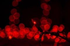 De abstracte Kerstboomlichten in donkere, rode bokeh, onduidelijk beeld defocused, defocused het onduidelijke beeld Royalty-vrije Stock Fotografie