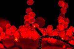 De abstracte lichten van de Kerstmisboom in donkere, rode bokeh Stock Afbeeldingen