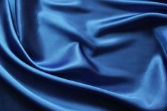 De abstracte vouwen van de achtergrond blauwe satijnstof Royalty-vrije Stock Afbeeldingen