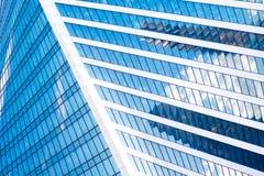 De abstracte wolkenkrabbers met bezinning in vensters blauwe hemel, witte wolken en zon schitteren Stock Foto