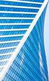 De abstracte wolkenkrabbers met de blauwe hemel van bezinningsð ¾ n vensters, witte wolken en zon schitteren Stock Afbeelding