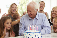 De abuelo sopla hacia fuera velas de la torta de cumpleaños en el partido de la familia imagenes de archivo