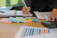 de accountant schrijft nota & gebruikt calculator om opbrengst & bu te berekenen royalty-vrije stock afbeeldingen
