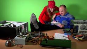 De achteloze de technicusman en vrouw hebben pret met tabletcomputer op het werk stock videobeelden
