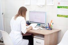 De achtereindmening van Kaukasische blondevrouw arts in witte eenvormig in het kliniekziekenhuis werkt aan computer Kabinet en an stock fotografie