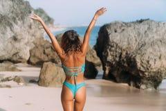 De achtereindmening van slank meisje in zwempak met opgeheven wapens staat op zandig strand met rotsen op royalty-vrije stock foto