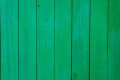De achtergrond is een houten die omheining met groene verf wordt geschilderd Royalty-vrije Stock Afbeeldingen