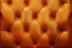 De achtergrond is een warm donkeroranje meubilair van het stofferingsleer, deur Naadloze leertextuur Stock Fotografie