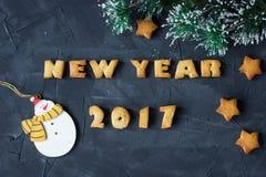 De achtergrond met het gebakken nieuwe jaar 2017 van peperkoekwoorden en star-shaped koekjes met sneeuwmannen en de verfraaide sp Royalty-vrije Stock Fotografie