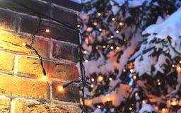 De achtergrond van bakstenen muurkerstmis met lichten het gloeien en sneeuw Stock Afbeeldingen