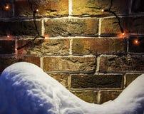 De achtergrond van bakstenen muurkerstmis met lichten het gloeien en sneeuwbank Royalty-vrije Stock Foto's