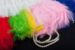 De achtergrond van de decoratie De zachte mooie kleurenveren en perl de halsband leggen op zwarte stof Stock Foto's