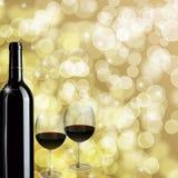 De Achtergrond van de Fles van de rode Wijn en van Bokeh van Twee Glazen Stock Foto