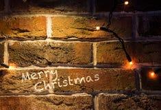 De achtergrond van de Kerstmisbakstenen muur met lichten gloeiende kaart Royalty-vrije Stock Afbeeldingen
