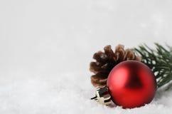 De Achtergrond van de Kerstmisgrens met Rode Snuisterij en Gebladerte op Sneeuw Royalty-vrije Stock Afbeelding