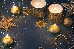 De achtergrond van de Kerstmisvakantie met kaarsen en gouden decoratie over donkere raad Stock Afbeelding