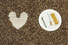 De achtergrond van de koffieboon met hart en vele sigaren op witte plaat Royalty-vrije Stock Afbeelding