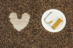 De achtergrond van de koffieboon met hart en vele sigaren op witte plaat Royalty-vrije Stock Foto
