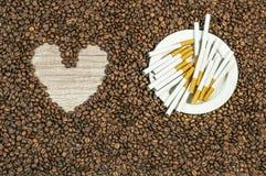 De achtergrond van de koffieboon met hart en vele sigaren op witte plaat Stock Afbeeldingen