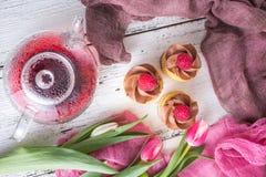 De achtergrond van de lente Cupcakes en thee op een lijst met roze tulpen Stilleven met vers boeket van tulpen concept dames ` te stock afbeeldingen