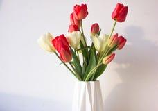 De achtergrond van de lente Tulpen in een witte vaas Stock Foto's