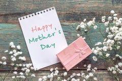 De achtergrond van de moedersdag met witte kleine bloemen, blocnotepagina Royalty-vrije Stock Foto