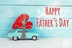 De achtergrond van de vadersdag met het miniatuur blauwe stuk speelgoed auto dragen hij Royalty-vrije Stock Afbeeldingen