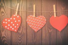 De achtergrond van de valentijnskaartendag Met de hand gemaakte stuk speelgoed harten die van een kabel op hout hangen Royalty-vrije Stock Afbeeldingen