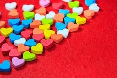 De achtergrond van de valentijnskaartendag met kleurrijk die hart op rode pape wordt gevormd Stock Afbeelding