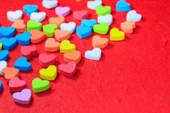 De achtergrond van de valentijnskaartendag met kleurrijk die hart op rode pape wordt gevormd Royalty-vrije Stock Afbeelding