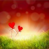 De achtergrond van de valentijnskaartendag met twee harten, gras met bokeh Stock Foto's