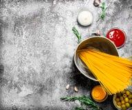 De achtergrond van deegwaren Oude spaghetti in de pan met kruiden en tomaten stock foto's