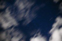 De achtergrond van donkerblauwe nachthemel met talloos fonkelt sterren en bewegende witte wolken op op het Royalty-vrije Stock Foto