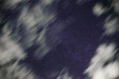 De achtergrond van donkerblauwe nachthemel met talloos fonkelt sterren en bewegende witte wolken op op het Stock Fotografie