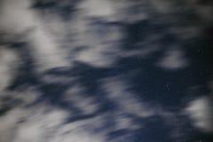 De achtergrond van donkerblauwe nachthemel met talloos fonkelt sterren en bewegende witte wolken op op het Royalty-vrije Stock Foto's