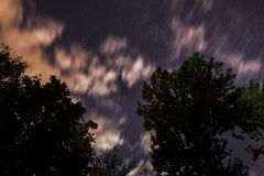 De achtergrond van donkerblauwe nachthemel met talloos fonkelt sterren en bewegende witte wolken op op het Stock Foto