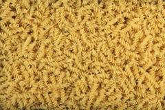 De achtergrond van gele Italiaanse deegwaren rolde omhoog in een spiraal Mening van hierboven Stock Foto