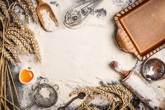 De achtergrond van het bloembaksel met ruw ei, de deegrol, het tarweoor en de plattelander bakken pan Stock Afbeeldingen