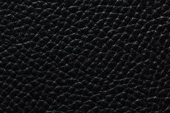 De achtergrond van het contrastleer in zwarte kleur De leertextuur van uitstekende kwaliteit stock afbeelding
