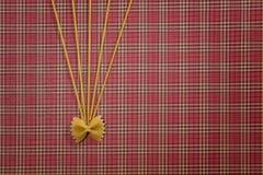 De achtergrond van het deegwarenpatroon Droog volkorenmeel farfalle en spaghetti op rood geregeld tafelkleed Vlak leg Hoogste men royalty-vrije stock afbeelding