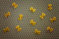 De achtergrond van het deegwarenpatroon Droog volkorenmeel farfalle op Kerstmisgrond Vlak leg Hoogste mening royalty-vrije stock foto's