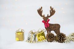 De achtergrond van het Kerstmisconcept, Houten rendier met giftdoos en denneappel over vaag bokeh stock foto's
