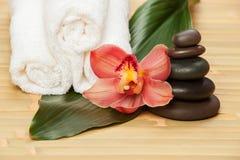 De achtergrond van het kuuroord Witte handdoeken op exotische installatie, mooie orchidee Royalty-vrije Stock Afbeeldingen
