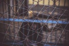 De achtergrond van het metaalnetwerk rabitz Vage achtergrond, primaten in een kooi dierentuin Royalty-vrije Stock Foto's