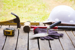 De achtergrond van het metselwerkhulpmiddel zoals handschoen en meetlint en voorhamer met troffel en niveau met helm en enz. stock foto's